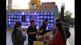 In this photo taken Sunday, Nov. 10, 2019, promoters hand out free gifts as part of a game to promote Nov. 11 Singles day in Beijing. Chinese online shoppers hunt bargains on Singles Day, a holiday invented in the 1990s that has become the world's busiest day for online commerce. (AP Photo/Ng Han Guan)
