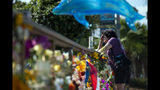 FILE - In this Sept. 4, 2019, file photo, a woman becomes emotional after placing flowers at a memorial for the victims of the Conception dive boat fire in the Santa Barbara Harbor in Santa Barbara, Calif. The widow of Justin Dignam, one of the 34 people who died in the fire, has filed a lawsuit against the boat's owners, making it the first claim from one of the 34 victims' families. (AP Photo/Christian Monterrosa, File)