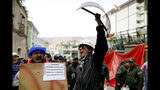 Opponents of former Bolivian President Evo Morales hold shields at a barricade set up by protesters outside presidential palace in La Paz, Bolivia, Monday, Nov. 11, 2019. Morales' Nov. 10 resignation, under mounting pressure from the military and the public after his re-election victory triggered weeks of fraud allegations and deadly demonstrations, leaves a power vacuum and a country torn by protests against and for his government. (AP Photo/Natacha Pisarenko)
