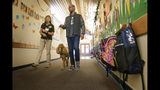 "In this Wednesday, Nov. 6, 2019, photo, Paws of Assitance Loving Support volunteer, Pam Frank, left, and ""Rudy,"" a support dog, are escorted by school principal, Jeff Franey to different classrooms at Healdsburg Elementary School in Healdsburg Calif. The children were greeted by Rudy on their first day back to school since the Kincade Fire. Many of the children suffer from PTSD due to the frequency of the fires in the area. (AP Photo/Lacy Atkins)"