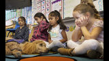 "In this Wednesday, Nov. 6, 2019, photo, Kindergartner Evangeline Flores, far right, looks eye in eye with ""Rudy,"" a support dog from Paws of Assitance Loving Support on the children's first day back to school since the Kincade Fire in Healdsburg, Calif. Many of the children suffer from PTSD symptoms due to the frequency of the fires in the area. (AP Photo/Lacy Atkins)"