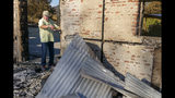 "In this Tuesday, Nov. 5, 2019, photo, Ken Wilson, owner of the Soda Rock Winery, measures the old stone facade of the winery's main building in Healdsburg, Calif. The building, destroyed by the Kincade wildfire, was originally a general store and post office, built in 1869. After the fire, Soda Rock owner Ken Wilson determined to save it and reinforce it to withstand earthquakes. Signs on the nearby roadside announced wine tastings: ""RECOVERY BEGINS!"" Many have stopped in. ""This is what I call resiliency!"" one customer said as he arrived. Wilson, a Canadian who moved to Sonoma County in 1979, explained that this was how he started tastings with his first winery in 1998, ""a plank and two barrels and we were in business. (AP Photo/Lacy Atkins)"