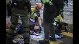 """Medical volunteers help an injured man after being attacked by pro-democracy protesters during a crash between protesters and police in Hong Kong, Monday, Nov. 11, 2019. Hong Kong's leader Carrie Lam has pledged to """"spare no effort"""" in bringing an end to anti-government protests that have wracked the city for more than five months, following a day of violence in which one person was shot and another set on fire. (AP Photo/Kin Cheung)"""
