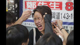 A woman reacts after being pepper sprayed by police in Hong Kong Monday, Nov. 11, 2019. Police in Hong Kong were filmed shooting at least one protester and possibly a second on Monday as demonstrators blocked subway lines and roads during the morning commute. (AP Photo/Kin Cheung)