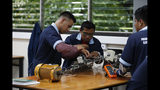 """In this Oct. 11, 2019, photo, José Fernando Guillén Rodríguez, 21, left, practices building circuits with other students around a workbench in San Salvador, El Salvador. """"I don't think about migrating anymore,"""" said Guillén Rodríguez, 21, who was apprehended in the U.S. at 18 and spent time in adult detention before being deported. Now he's completed a year of daily electrical classes and works as an apprentice at an electrical construction company. (AP Photo/Eduardo Verdugo)"""