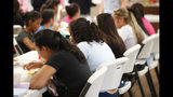 In this Sept. 24, 2019 photo, girls eat lunch at a shelter for migrant teenage girls, in Lake Worth, Fla. The nonprofit U.S. Committee for Refugees and Immigrants opened the federally funded Rinconcito del Sol shelter this summer, aiming to make it a model of excellence in a system of 170 detention centers, residential shelters and foster programs which held nearly 70,000 migrant kids in the past year. (AP Photo/Wilfredo Lee)