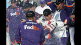 Denny Hamlin, center, gets sprayed with champagne by pit crew members in Victory Lane after he won the NASCAR Cup Series auto race Sunday, Nov. 10, 2019, in Avondale, Ariz. (AP Photo/Ralph Freso)