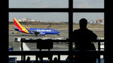 FILE- In this Jan. 25, 2019, file photo a Southwest Airlines jet moves on the runway as a person eats at a terminal restaurant at LaGuardia Airport in New York. Federal regulators have threatened to ground dozens of Southwest Airlines jets if the airline can't confirm that the planes, which it bought used from foreign operators, meet all safety standards. (AP Photo/Julio Cortez, File)