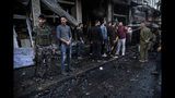 People check the aftermath of a car bomb blast in the city of Qamishli, northern Syria, Monday, Nov. 11, 2019. Three car bombs went off Monday in then city killing several and wounding tens of people. (AP Photo/Baderkhan Ahmad)