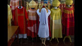 In this Friday, Nov. 8, 2019, photo, Sister Sukanya Sukchai adjusts a newly made chasubles at Catholic preparatory school in Bangkok, Thailand. Seamstresses from the Congregation of the Sacred Heart of Jesus Sisters of Bangkok are studiously snipping and sewing, fashioning robes for the upcoming visit of Pope Francis. They've been working tirelessly, running up the ceremonial garments Pope Francis will wear during his four-day visit to Thailand later this month. (AP Photo/Gemunu Amarasinghe)