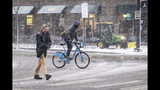 A pedestrian walks in the snow as a winter weather advisory is issued for the Chicago area on Monday, Nov. 11, 2019, in Chicago. (Rich Hein/Chicago Sun-Times via AP)