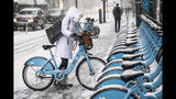 A woman clears off a Divvy bike as a winter weather advisory is issued for the Chicago area on Monday, Nov. 11, 2019, in Chicago. (Rich Hein/Chicago Sun-Times via AP)