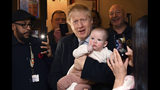 Britain' Prime Minister Boris Johnson holds a baby as he meets with supporters at the Lych Gate Tavern in Wolverhampton, England, Monday, Nov. 11, 2019 as part of the General Election campaign trail. Britain goes to the polls on Dec. 12. (Ben Stansall/Pool Photo via AP)