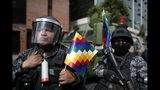 "A police officer holds a ""wiphala"" flag, representing indigenous people, that he was given by supporters of former President Evo Morales who are marching in La Paz, Bolivia, Tuesday, Nov. 12, 2019. Former President Evo Morales, who transformed Bolivia as its first indigenous president, flew to exile in Mexico on Tuesday after weeks of violent protests, leaving behind a confused power vacuum in the Andean nation. (AP Photo/Natacha Pisarenko)"