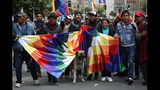 "A dog stands with supporters of Bolivia's former President Evo Morales holding a ""wiphala"" flag that represents indigenous people during a march in La Paz, Bolivia, Tuesday, Nov. 12, 2019. Former President Evo Morales, who transformed Bolivia as its first indigenous president, flew to exile in Mexico on Tuesday after weeks of violent protests, leaving behind a confused power vacuum in the Andean nation. (AP Photo/Natacha Pisarenko)"