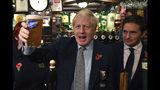 Britain' Prime Minister Boris Johnson raises a pint of beer, as he meets with military veterans at the Lych Gate Tavern in Wolverhampton, England, Monday, Nov. 11, 2019 as part of the General Election campaign trail. Britain goes to the polls on Dec. 12. (Ben Stansall/Pool Photo via AP)