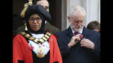 Britain's main opposition Labour Party leader Jeremy Corbyn adjusts his poppy, as he waits outside Islington Town Hall with Islington's Mayor Rakhia Ismail, ahead of observing a silence to mark Armistice Day, the anniversary of the end of the First World War, in London, Monday Nov. 11, 2019. Britain's Brexit is one of the main issues facing voters as political leaders tour the country ahead of a General Election on Dec. 12. (Jonathan Brady/PA via AP)
