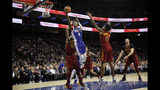 Philadelphia 76ers' Josh Richardson (0) goes up for a shot between Cleveland Cavaliers' Tristan Thompson (13) and Kevin Porter Jr. (4) during the first half of an NBA basketball game, Tuesday, Nov. 12, 2019, in Philadelphia. (AP Photo/Matt Slocum)