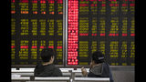In Monday, Nov. 11, 2019, photo, investors monitor stock prices at a brokerage in Beijing. Shares were mixed in Asia on Tuesday, Nov. 12, as investors awaited cues on trade talks between China and the U.S. (AP Photo/Ng Han Guan)