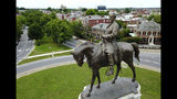 FILE- In this June 27, 2017 file photo a statue of Confederate General Robert E. Lee stands in the middle of a traffic circle on Monument Avenue in Richmond, Va. Virginia Democrats seized control of the General Assembly last week and that means Confederate statues could soon be coming down in a state that's full of them. (AP Photo/Steve Helber, File)