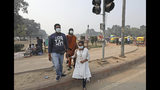 Tourists wear masks to save themselves from pollution as they cross a road in New Delhi, India, Tuesday, Nov. 12, 2019. A thick haze of polluted air is hanging over India's capital, with authorities trying to tackle the problem by sprinkling water to settle dust and banning some construction. The air quality index exceeded 400, about eight times the recommended maximum. (AP Photo/Manish Swarup)