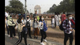 Foreign tourists wear masks to save themselves from pollution as they cross a road in New Delhi, India, Tuesday, Nov. 12, 2019. A thick haze of polluted air is hanging over India's capital, with authorities trying to tackle the problem by sprinkling water to settle dust and banning some construction. The air quality index exceeded 400, about eight times the recommended maximum. (AP Photo/Manish Swarup)