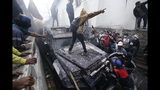 FILE - In this Oct. 9, 2019, file photo, anti-government demonstrators commandeer an armored vehicle during a nationwide strike against President Lenin Moreno and his economic policies in Quito, Ecuador. From Honduras to Chile, popular frustration with anemic economic growth, entrenched corruption and gaping inequality is driving the region's middle classes to rebel against incumbents of all ideological bents in what has been dubbed by some the Latin American Spring. (AP Photo/Carlos Noriega, File)