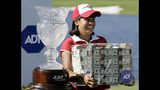 FILE - In this Nov. 19, 2006 file photo Julieta Granada, of Paraguay, stands next to her trophy as she holds a box of money after winning the LPGA ADT Championship at the Trump International Golf Club in West Palm Beach, Fla. The format this year allows any of the 60 players to win the $1.5 million prize by winning the CME Group Tour Championship. (AP Photo/Lynne Sladky, file)