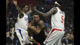 Toronto Raptors guard Norman Powell drives between Los Angeles Clippers guard Lou Williams, left, and forward Montrezl Harrell during the first half of an NBA basketball game in Los Angeles, Monday, Nov. 11, 2019. (AP Photo/Chris Carlson)
