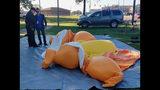 Un policía y un hombre no identificado, de pie junto a un globo con forma de caricatura de Donald Trump, desinflado luego de ser tajeado por una persona en el Parque Monnish cuando varias personas protestaban por la visita del presidente de Estados Unidos a un partido universitario de fútbol americano entre Louisiana State y Alabama, que se disputaba cerca en Tuscaloosa, Alabama, el sábado 9 de noviembre de 2019. (Stephanie Taylor/The Tuscaloosa News via AP)