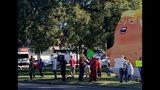 Gente de pie junto a un globo que muestra una caricatura de Donald Trump, durante una protesta en el Parque Monnish contra la visita del presidente de Estados Unidos a un partido universitario de fútbol americano entre Louisiana State y Alabama, que se disputaba cerca, en Tuscaloosa, Alabama, el sábado 9 de noviembre de 2019. (Stephanie Taylor/The Tuscaloosa News via AP)