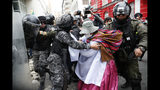 A backer of former President Evo Morales scuffles with police in La Paz, Bolivia, Wednesday, Nov. 13, 2019. The opposition senator who has claimed Bolivia's presidency Jeanine Anez, faces the challenge of stabilizing the nation and organizing national elections within three months at a time of political disputes that pushed Morales to fly off to self-exile in Mexico after 14 years in power. (AP Photo/Natacha Pisarenko)