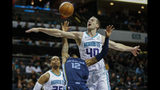Charlotte Hornets center Cody Zeller, right, fouls Memphis Grizzlies guard Ja Morant in the first half of an NBA basketball game in Charlotte, N.C., Wednesday, Nov. 13, 2019. (AP Photo/Nell Redmond)