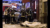 FILE - In this Friday, Nov. 13, 2015 file photo, rescue workers tend to victims outside a cafe in the 10th district of Paris. France is commemorating the fourth anniversary of the Islamic State attacks in Paris. The attacks on Nov. 13, 2015, left 131 people dead at the country's national stadium, the Bataclan concert hall and bars and restaurants in the city center. (AP Photo/Jacques Brinon, file)