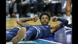 Ja Morant, base de los Grizzlies de Memphis, muestra sus bíceps luego de recibir una falta en el encuentro ante los Hornets de Charlotte, el miércoles 13 de noviembre de 2019 (AP Foto/Nell Redmond)