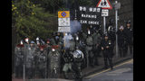 Riot police fire tear gas gun as they face-off with pro-democracy protesters at the campus of the Hong Kong Polytechnic University, in Hong Kong, Thursday, Nov. 14, 2019. University students from mainland China and Taiwan are fleeing Hong Kong, while those from three Scandinavian countries have been moved or urged to leave as college campuses become the latest battleground in the city's 5-month-long anti-government unrest. (AP Photo/Ng Han Guan)