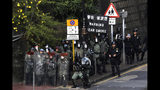 A riot police, center, aims his tear gas gun during a face-off with pro-democracy protesters at the campus of the Hong Kong Polytechnic University, in Hong Kong, Thursday, Nov. 14, 2019. University students from mainland China and Taiwan are fleeing Hong Kong, while those from three Scandinavian countries have been moved or urged to leave as college campuses become the latest battleground in the city's 5-month-long anti-government unrest. (AP Photo/Ng Han Guan)