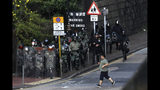 A man runs past riot policemen gathering near the campus of the Hong Kong Polytechnic University as they face-off with pro-democracy protesters in Hong Kong, Thursday, Nov. 14, 2019. University students from mainland China and Taiwan are fleeing Hong Kong, while those from three Scandinavian countries have been moved or urged to leave as college campuses become the latest battleground in the city's 5-month-long anti-government unrest. (AP Photo/Ng Han Guan)