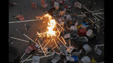 A protester tries to pour water on a fire burning amid debris placed to block a road leading to the Cross-Harbour Tunnel in Hong Kong, Thursday, Nov. 14, 2019. University students from mainland China and Taiwan are fleeing Hong Kong, while those from three Scandinavian countries have been moved or urged to leave as college campuses become the latest battleground in the city's 5-month-long anti-government unrest. (AP Photo/Ng Han Guan)