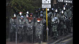 Riot police stand guard as they face off with pro-democracy protesters at the campus of the Hong Kong Polytechnic University, in Hong Kong, Thursday, Nov. 14, 2019. University students from mainland China and Taiwan are fleeing Hong Kong, while those from three Scandinavian countries have been moved or urged to leave as college campuses become the latest battleground in the city's 5-month-long anti-government unrest. (AP Photo/Ng Han Guan)