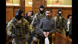 A Syrian man identified as Hassan F., centre, is escorted by Police officers as he arrives at the Metropolitan Court in Budapest, Hungary, Wednesday, Nov. 13, 2019. Prosecutors said the 27-year-old man identified only as Hassan F. participated in the beheading of a religious leader in the city of al-Sukhnah in Homs province and was also involved in the killings of at least 25 people. (Zsolt Szigetvary/MTI via AP)