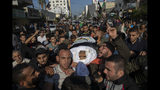 Palestinians chant angry slogans as they carry the body of Islamic Jihad commander, Bahaa Abu el-Atta, who was killed with his wife by an Israeli missile strike on their home, during his funeral in Gaza City, Tuesday, Nov. 12, 2019. (AP Photo/Khalil Hamra)