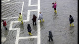 People walk in a flooded St. Mark's Square, in Venice, Italy, Tuesday, Nov. 12, 2019. The high tide reached a peak of 127cm (4.1ft) at 10:35am while an even higher level of 140cm(4.6ft) was predicted for later Tuesday evening. (AP Photo/Luca Bruno)