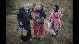 Tres mujeres que visten atuendos típicos bromean mientras participan en la cosecha de azafrán en Askaoun, Marruecos, el 5 de noviembre del 2019. (AP Photo/Mosa'ab Elshamy)