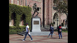 FILE - In this March 12, 2019, file photo, people pose for photos in front of the iconic Tommy Trojan statue on the campus of the University of Southern California in Los Angeles. The death of nine students since classes began a little more than two months ago has left students and administrators at the University Southern California shaken and seeking answers. The Los Angeles Times reports the latest death was discovered Monday, Nov. 11, 2019, when the body of a 27-year-old student was found in an off-campus apartment. (AP Photo/Reed Saxon, File)