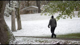 A walker takes a stroll through the light snow at Steele Creek Park in Bristol Tennessee on Tuesday, Nov. 12, 2019. Following the light snowfall, temperatures began to drop throughout the day with record cold expected overnight. (Andre Teague/Bristol Herald Courier via AP)