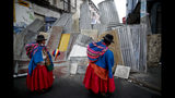 Supporters of former President Evo Morales stand at a barricaded stretch leading to the presidential palace during a march in La Paz, Bolivia, Thursday, Nov. 14, 2019. Morales resigned and flew to Mexico under military pressure following massive nationwide protests over alleged fraud in an election last month in which he claimed to have won a fourth term in office. (AP Photo/Natacha Pisarenko)