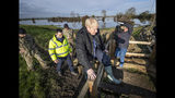 Britain's Prime Minister Boris Johnson, clambers over a fence, during a visit to see the effects of recent flooding, in Stainforth, England, Wednesday, Nov. 13, 2019. (Danny Lawson/Pool Photo via AP)