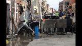 A woman jumps over a puddle during cleaning following a flooding in Venice, Italy, Thursday, Nov. 14, 2019. The worst flooding in Venice in more than 50 years has prompted calls to better protect the historic city from rising sea levels as officials calculated hundreds of millions of euros in damage. The water reached 1.87 meters above sea level Tuesday, the second-highest level ever recorded in the city. (Andrea Merola/ANSA via AP)