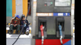 Workers sit at a gas station in La Paz, Bolivia, Thursday, Nov. 14, 2019. Gas stations have run out of fuel as the result of followers of former President Evo Morales blocking the main highway. (AP Photo/Natacha Pisarenko)